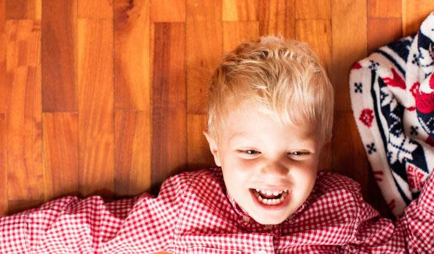 smiling-kid-on-the-wooden-floor_1194-430